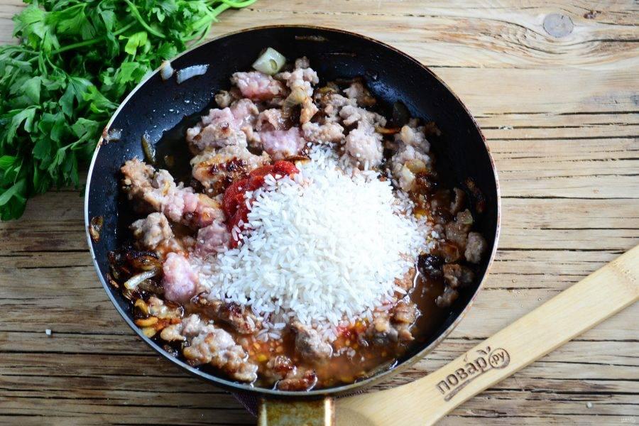 Затем добавьте в сковороду рис (сырой), томатную пасту и мякоть помидоров, слегка посолите и поперчите.