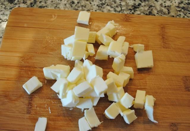 2. Пару минут нужно взбить все, а параллельно нарезать небольшими кубиками сливочное масло, предварительно охладив его.