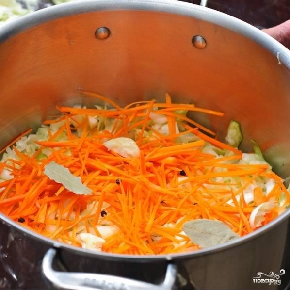 Когда перемешанная руками капуста начнет выпускать жидкость, можно приступать к следующему шагу. Берем большую кастрюлю. Выкладывать капусту и морковь я рекомендую слоями. Для такого количества ингредиентов хватит трех слоев. Итак, на дно кастрюли выкладываем треть нашей капусты, сверху - треть моркови. Далее - пара зубчиков чеснока, чайная ложка перца горошком и два лавровых листа.