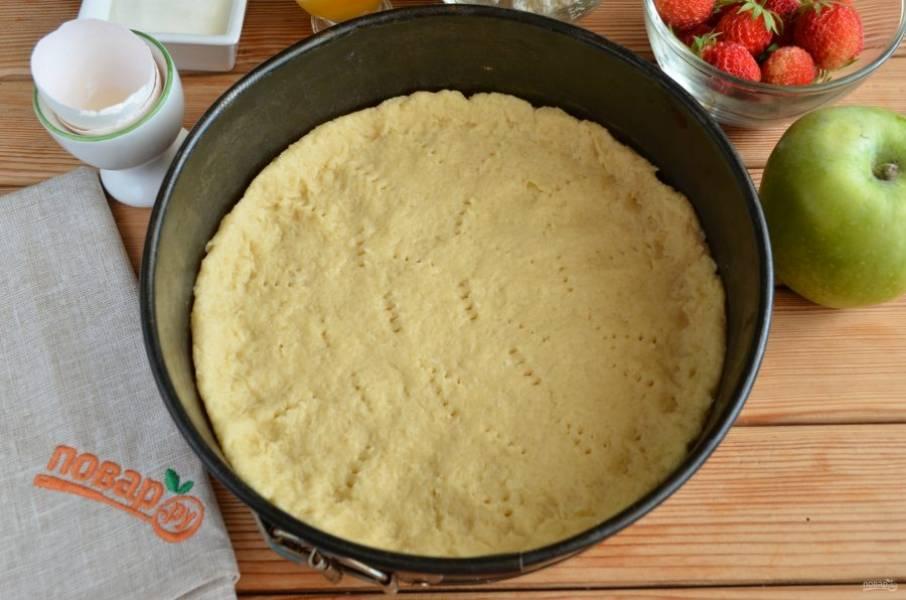 Возьмите антипригарную форму, распределите тесто тонким слоем по всей поверхности формы, сделайте небольшие бортики. Проткните вилочкой тесто, чтобы не вздувалось во время выпечки. В горячую духовку поставьте форму на 20 минут, температура — 180 градусов.