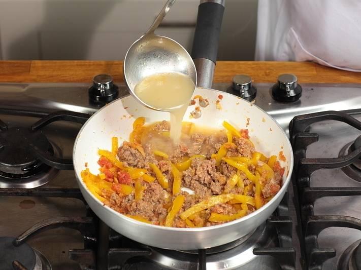 После обжарки фарша влейте бульон и добавьте специи.
