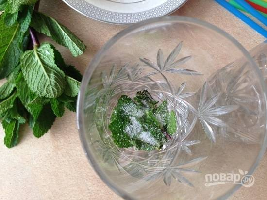 Обрываем с веточки листики мяты, рвем их руками и раскладываем по стаканам. Добавим сахар и слегка примнем листики с сахаром.