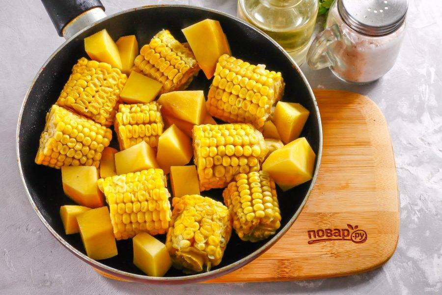 Очистите картофель и лук от кожуры и промойте в воде. Если используете морковь или другие овощи, требующие очистки, то так же очистите и промойте их. Нарежьте клубни картофеля средними кубиками, а промытые початки кукурузы разрежьте на 3-4 части. Влейте растительное масло на сковороду и прогрейте. Выложите нарезки и обжарьте их в течение 10-12 минут до полуготовности.