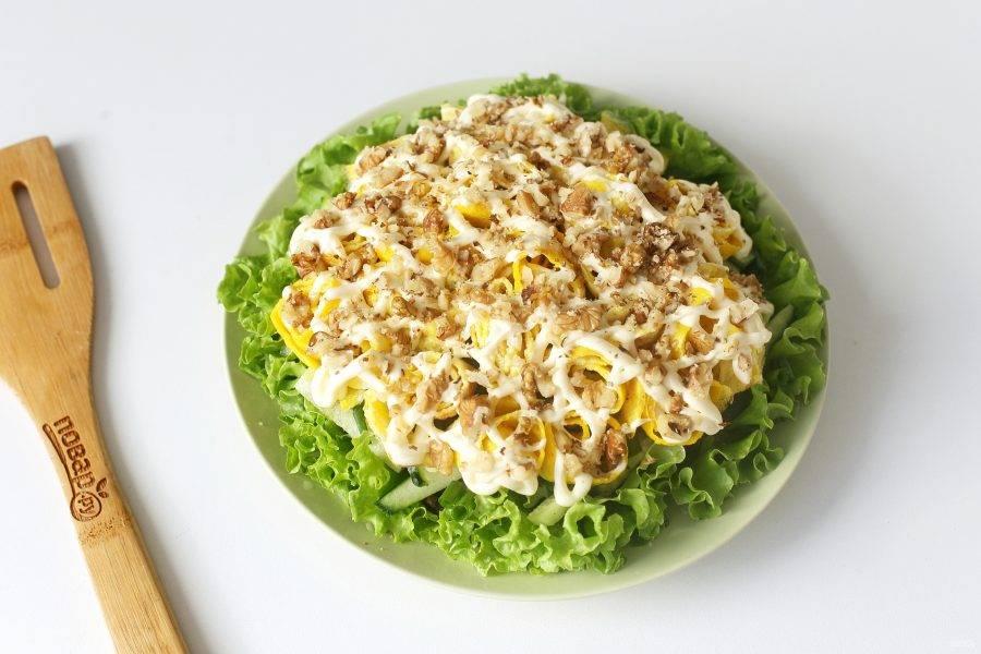 Сделайте сетку из майонеза, и украсьте салат измельченными грецкими орешками.