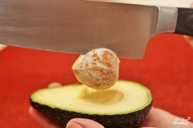 Авокадо разрезаем пополам, ножом ударяем по косточке (она мягкая, поэтому нож в ней застревает), проворачиваем нож и с легкостью вынимаем косточку. Затем авокадо очищаем от шкурки и нарезаем кубиками.