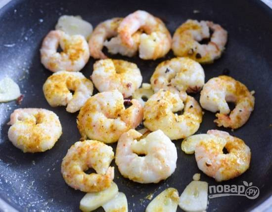 Выкладываем на сковороду размороженные креветки, посыпаем карри и паприкой, обжариваем примерно по 1,5-2 минуты с каждой стороны.