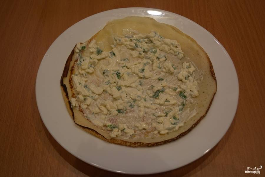 На подготовленную тарелку кладем первый блин. Сырную массу перемешиваем, 2-3 ст. ложки массы кладем на блин и размазываем.