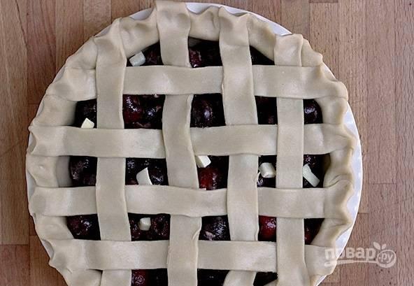 5. Оставшееся тесто раскатайте, нарежьте средними полосочками, которыми накройте начинку. Все, можно отправлять форму в духовку и выпекать пирог.