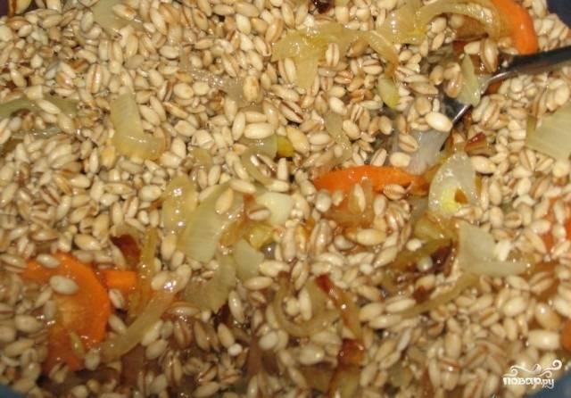 3.После установленного времени с перловки сливаем воду и добавляем к ней обжаренные овощи, перемешиваем.