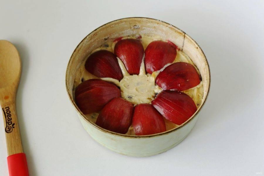 Яблоки разрежьте на 4 части. Сделайте глубокие надрезы ножом, выложите их сверху и слегка утопите в тесте. Выпекайте пирог в духовке при температуре 190 градусов около 45 минут.