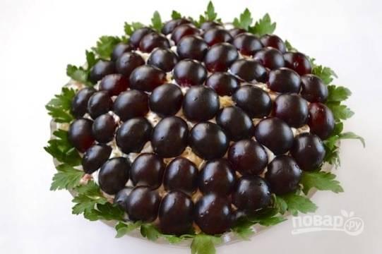Виноград разрезаем пополам, удаляем косточки. Красиво выкладываем виноградинки по всему салату. По краю салатницы выкладываем листья петрушки. Затем отправляем салат в холодильник на 1-2 часа.