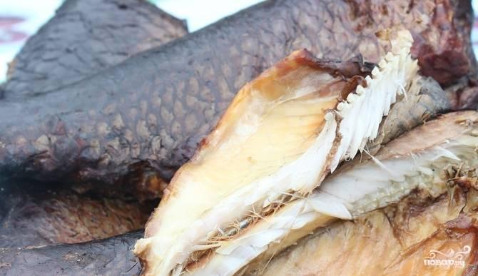 4.Накройте коптильню крышкой и установите сверху мангала. Готовится карп копченый полтора часа. Лучше через половину времени перевернуть рыбу на другой бок. Подавайте блюдо холодным.