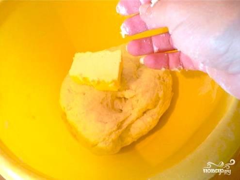 Разводим дрожжи в остальной части молока и добавляем их в тесто. Размешиваем. Кладем по кусочкам 100 грамм сливочного масла, добавляя его постепенно в процессе замеса. Когда все масло уйдет, добавьте оставшуюся муку. Замесите крепкое тесто.