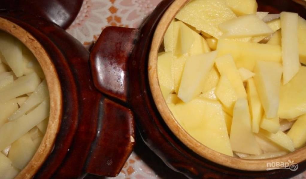 В горшочки кладем порезанный кубиками картофель.