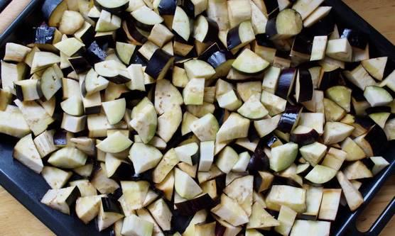 1. Баклажаны нужно вымыть, обсушить и нарезать кубиками. Их можно обжарить на сковороде до золотистой корочки, а можете выложить на противень, сбрызнуть растительным маслом и отправить в разогретую духовку.