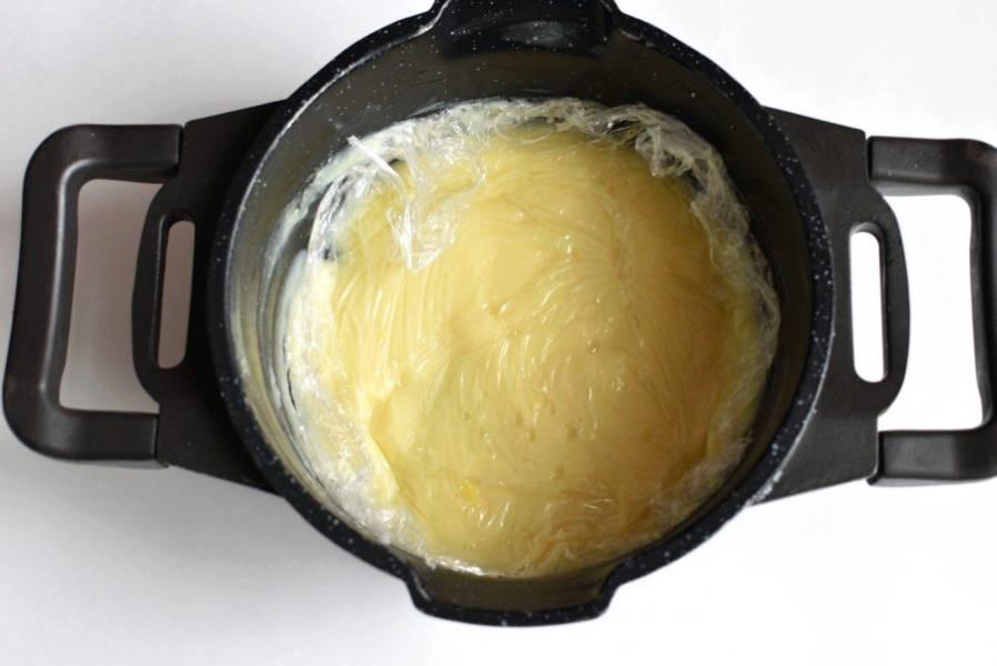 Приготовление пирога начните с заварного крема. Смешайте крахмал с сахаром и ванильным сахаром, влейте треть молока и тщательно перемешайте. Доведите оставшееся молоко до кипения и вылейте в него крахмальную смесь. Интенсивно помешивая, проварите крем до загустения. Накройте готовый крем пищевой пленкой впритык и охладите до комнатной температуры.