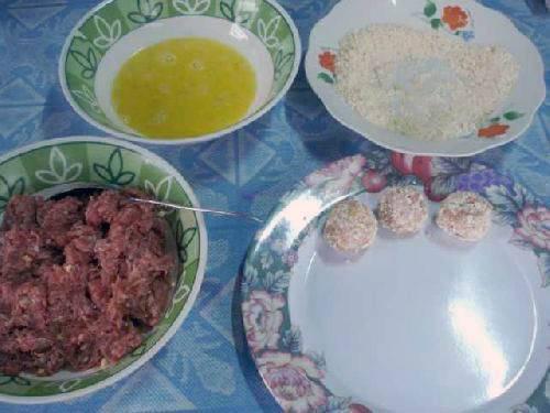 Приправить говядину солью, перцем, чесноком и луком. Перемешиваем. Лепим мясные шарики. Окунаем их во взбитое яйцо. Смешайте хлебные крошки и кукурузный крахмал. Раскатайте мясные шарики в крошках.