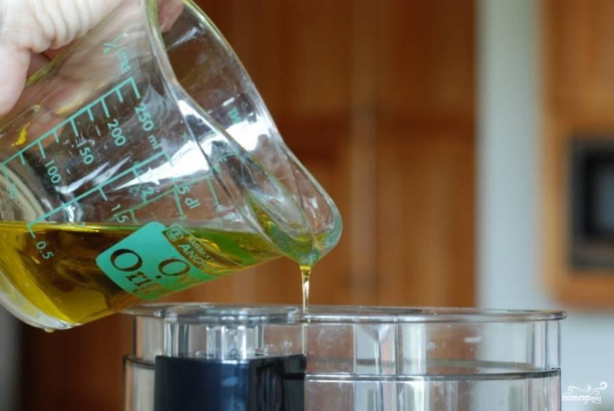 Затем, продолжая измельчать на медленной скорости, вводим в смесь оливковое масло. Постепенно масса должна стать гладкой и однородной.