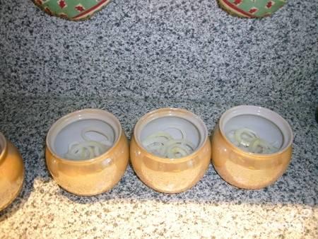 Выкладываем его в горшочки, сверху посыпаем солью и специями, я обычно использую только черный молотый перец. Лук нарезаем кольцами и кладем сверху.