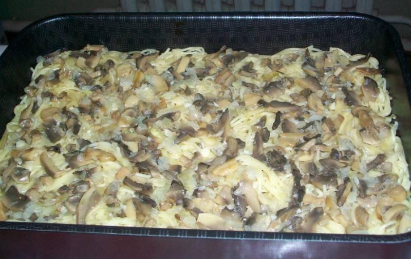 Затем выкладываем на макароны обжаренные грибы с луком.