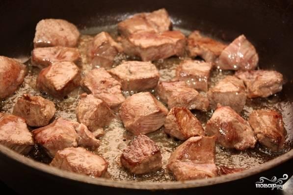1. Рецепт приготовления телятины в горшочке следует начать с мяса. Его необходимо вымыть и просушить. Нарезать порционными кусочками и отправить на сковороду с хорошо разогретым растительным маслом.