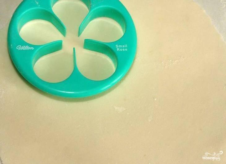 Цветочную пасту раскатайте в пласт. Вырежьте из неё детальки в виде лепестков для розы.