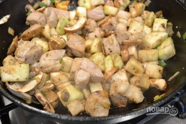 3. Если вы используете баклажан, заранее очистите, нарежьте его кубиками и посолите. Затем промойте под проточной водой и обсушите. Выложите на сковороду баклажан и грибочки. Жарьте еще минут 5.