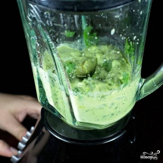 Начнем с приготовления заправки: добавим в чашу блендера очищенные авокадо, лук-шалот, перец серрано, воду, сок полутора лимонов, оливковое масло, кинзу, соль и перец. Измельчаем до однородности.