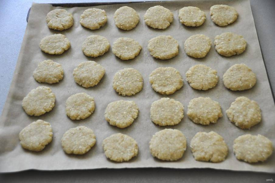 Отщипывайте комок теста размером с грецкий орех, делайте из него лепешечку и укладывайте на лист для выпечки.