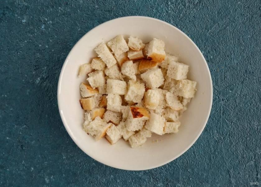 Хлеб нарежьте на мелкие кубики, добавьте масло и сухой чеснок, посолите по вкусу. Подсушите хлеб в духовке 15 минут при температуре 150 градусов.