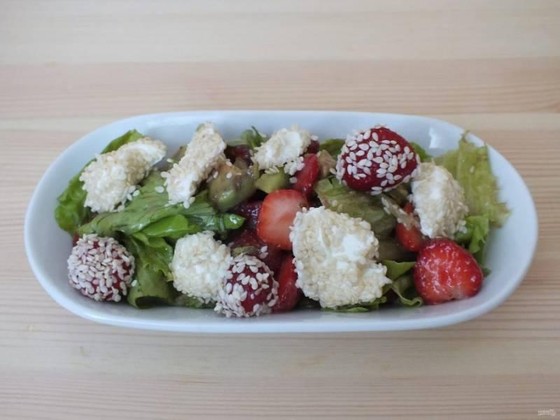 Выберите способ подачи. Мне больше нравится индивидуальный. В салатник меньшего размера положите часть основы, добавьте сыр в кунжуте и дополните ягодами клубники.