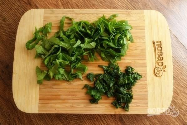 Листья одуванчика залейте соленой холодной водой с добавлением лимонного сока на 10 минут, чтобы ушла лишняя горечь. Зелень одуванчика и щавель нарежьте полосками.