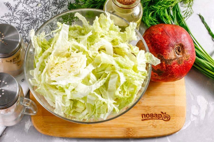 Пекинскую капусту промойте в воде и нашинкуйте ее половину, выкладывая нарезку в глубокую миску. Если у вас большая семья, то дорежьте и вторую половину овоща.