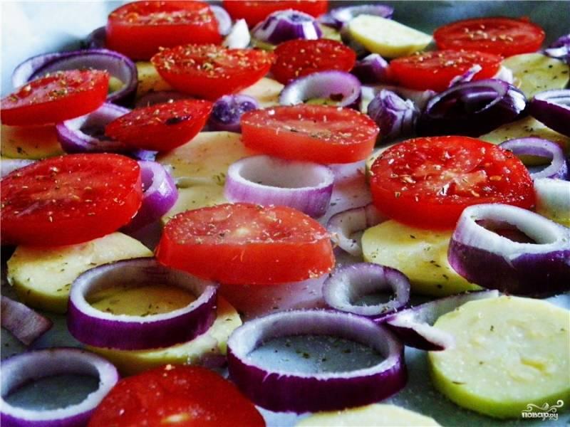 Помидоры вымойте и нарежьте колечками толщиной около двух сантиметров. Лук очистите от шелухи и тоже нережьте кольцами, но немного тоньше, чем помидоры. Молодой кабачок очистите и нарежьте кольцами или произвольными кусочками, слегка присыпьте солью. На противень, смазанный растительным маслом, выложите подушку из овощей: сначала кабачок, затем лук и помидоры.