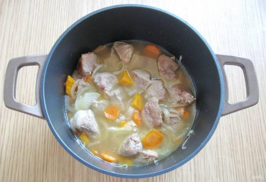 В течение 10 минут жарьте овощи с мясом, периодически перемешивая. После налейте бульон, накройте кастрюлю крышкой и тушите свинину почти до готовности.