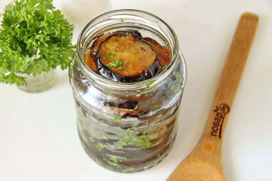 В стерилизованные банки выложите обжаренные баклажаны, пересыпая их солью и зеленью.