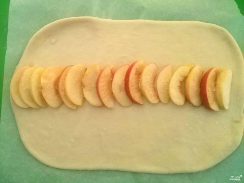 Яблоко порежьте на тонкие ломтики. Выложите его красиво на середину прямоугольника, посыпьте сахаром.