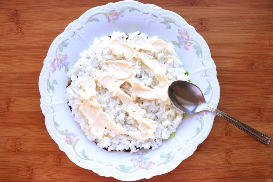 Сверху салата выложите слой риса, смажьте его майонезом.