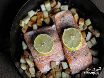 По истечении 15 минут, достаем нашу рыбу из духовки и перекладываем ее к картофелю в сковородку. На рыбу кладем да новых колечка лимона (старые выбрасываем), а картофель поливаем рыбным соком (из фольги) и отправляем обратно в духовку примерно на 5-7 минут. После чего достаем ее, раскладываем по тарелкам и наслаждаемся. Приятного аппетита!