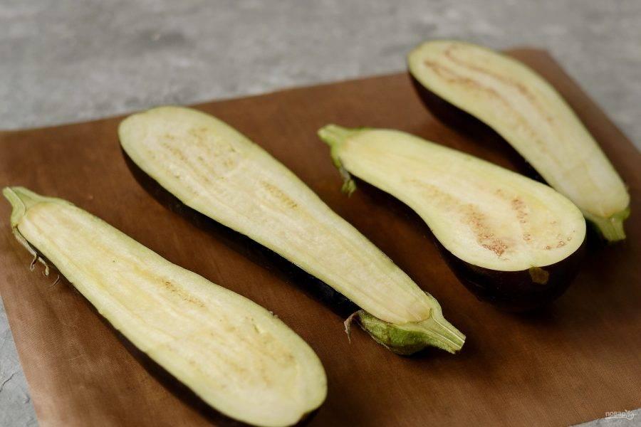 Баклажаны помойте, разрежьте пополам. Смажьте срезы растительным маслом. Запекайте баклажаны в разогретой до 200 градусом духовке до мягкости. Примерно 30-45 минут.