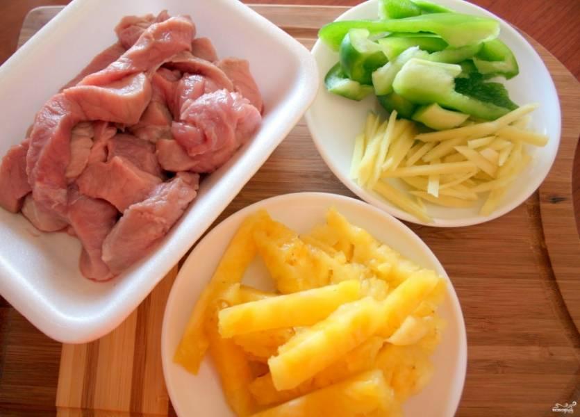 Ананас, имбирь, перец порежьте соломкой.  Свинину порежьте продолговатыми кусочками (как на бефстроганов), замаринуйте в соевом соусе (пара столовых ложек), яичном желтке, добавьте черный перец и щепотку крахмала. Оставьте мясо мариноваться на 30 минут.