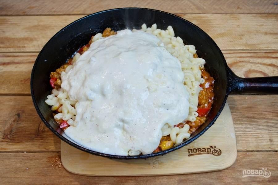 Влейте соус и добавьте еще немного натертого сыра.