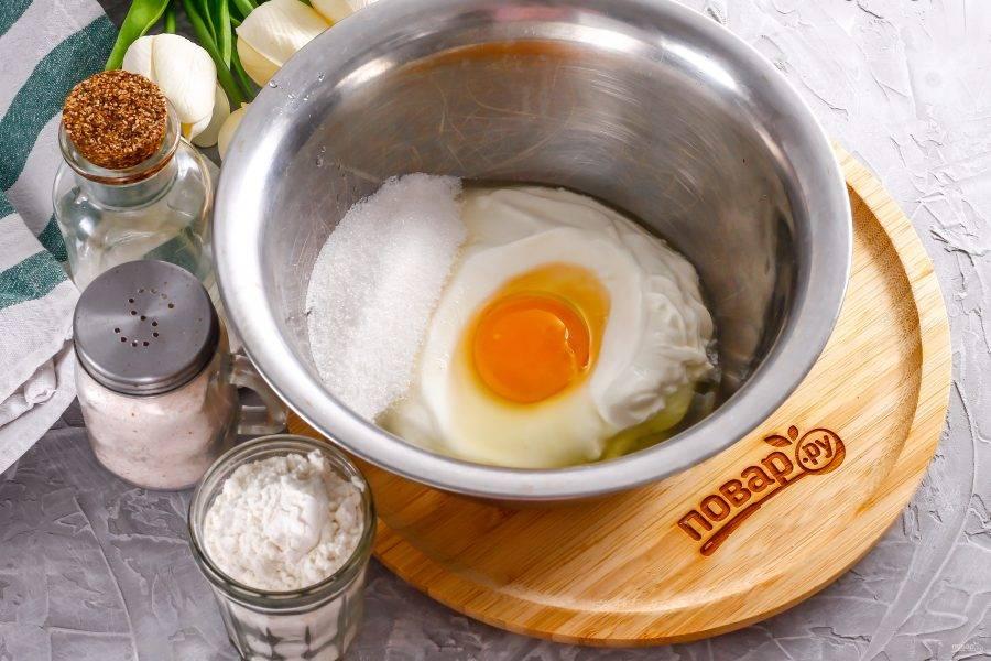 Выложите сметану в глубокую емкость, вбейте туда же куриное яйцо, всыпьте сахар и соль. Влейте воду и тщательно взбейте венчиком.