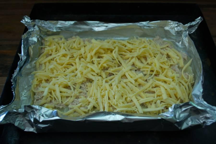 На крупной терке натрите твердый сыр. Посыпьте им запеканку. Посолите, поперчите. Разогрейте духовку до 200 градусов.