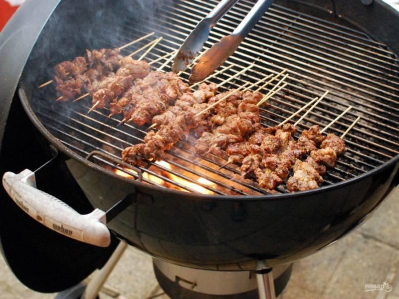 Нанизайте мясо на шпажки и отправьте жариться на небольшой огонь.