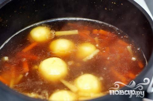 4. После этого добавить морковь и пастернак и варить около 5 минут.  Затем с помощью ложки выложить тесто, формируя  маленькие шарики. Вы можете делать это влажными руками, чтобы получились более ровные шарики. Варить примерно от 4 до 5 минут, пока клецки не затвердеют. Разлить суп по тарелкам и сразу подавать.