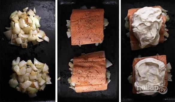 2. Выложите лук в жаропрочную форму. Это будет подушка для рыбы. Филе вымойте, обсушите, посолите и поперчите по вкусу. Выложите на лук и сверху распределите сметану.
