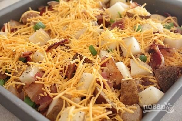 3. Сверху выложите вторую половину картофеля. Снова соль, перец, половина оставшегося сыра и бекона, зелень. Полейте сливками, добавьте немного сливочного масла сверху. Накройте форму фольгой и отправьте её в духовку.