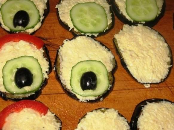 Каждый кружок баклажана намажем салатной массой. На один конец кружка выложим кружочек огурца и сверху уложим половинку маслины. На противоположный конец выкладываем по самому краю полоску перца.