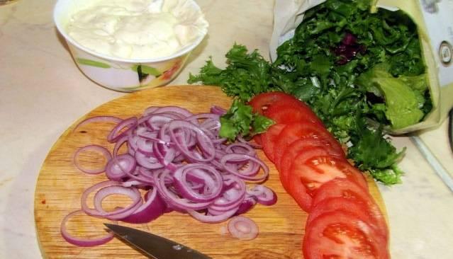 Тонкими колечками нарезаем лук и помидоры.